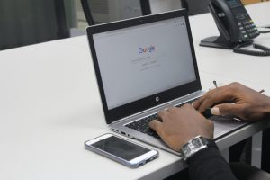 hands typing on a laptop that's opened to the google search page