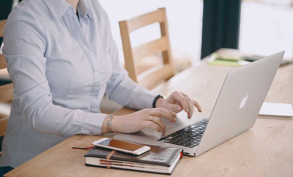 Woman at desk creating content on computer